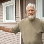 Dunite Historian and Author Norm Hammond in front of Dunite Cabin, Oceano