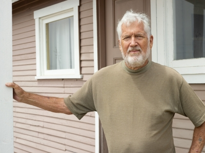 Dunite Historian and Author Norm Hammond in front of last remaining Dunite cabin, Oceano, CA